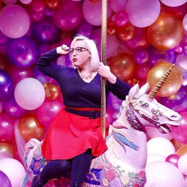 Photo of Hannah Day lead designer riding a unicorn with balloons in the. background
