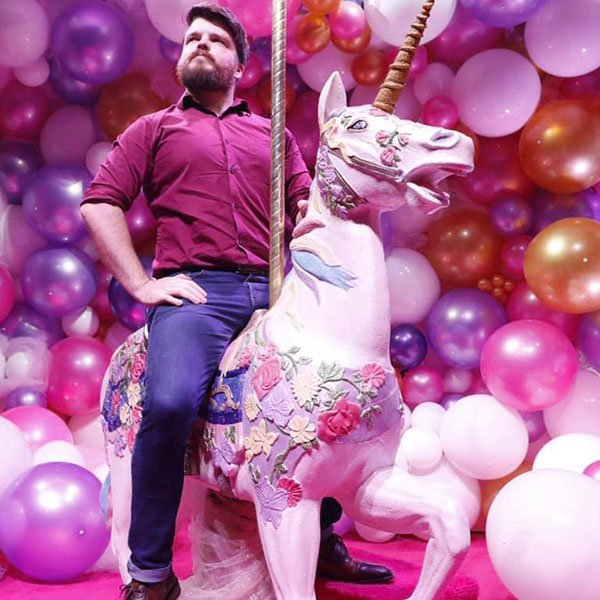 Photo of Lead photographer William Twitty on a unicorn with balloons in the background